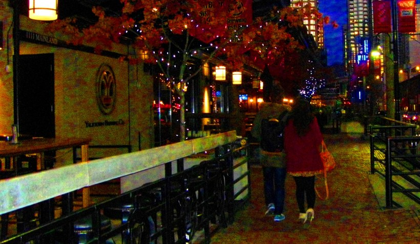 Yaletown Vancouver - Strolling arm-in-arm as they walk down the cobbled walkway.